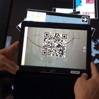 Une main déplace et manipule des fichiers sur une table tactile. Un QRcode photographié à l'aide d'une tablette permet de récupérer le contenu multimédia
